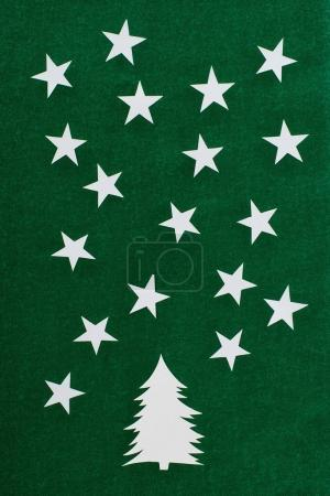 decorative paper christmas tree and stars on green background