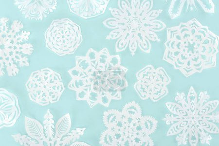 christmas background with decorative paper snowflakes, isolated on light blue