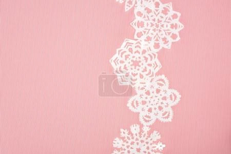 christmas background with decorative paper snowflakes on pink
