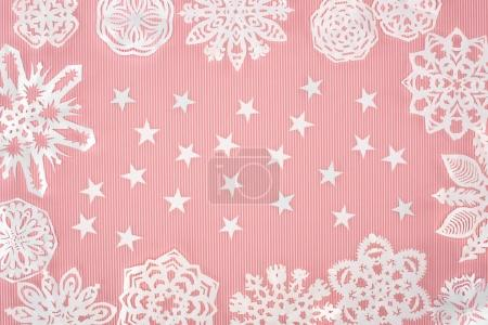 christmas background with paper snowflakes and stars on pink