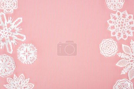 Photo pour Fond de Noël avec des flocons de neige en papier sur rose - image libre de droit