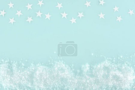 christmas background with decorative snow and stars, isolated on light blue