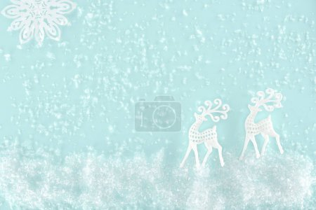 christmas background with decorative snow, snowflake and paper deer, isolated on light blue