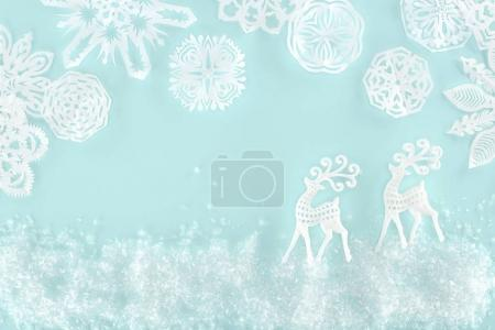 christmas background with decorative snow, snowflakes and paper deer, isolated on light blue