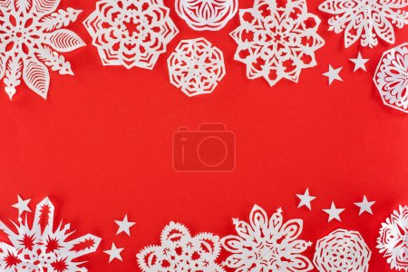 christmas background with white paper snowflakes, isolated on red with copy space