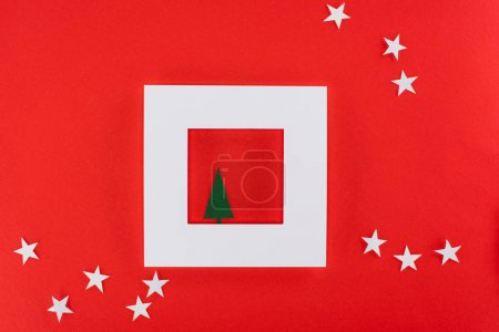 christmas tree in white frame with stars around, isolated on red