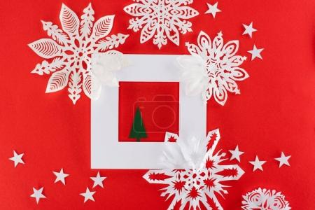 christmas tree in white frame with stars and paper snowflakes around, isolated on red