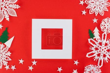 white frame with christmas trees, stars and paper snowflakes around, isolated on red