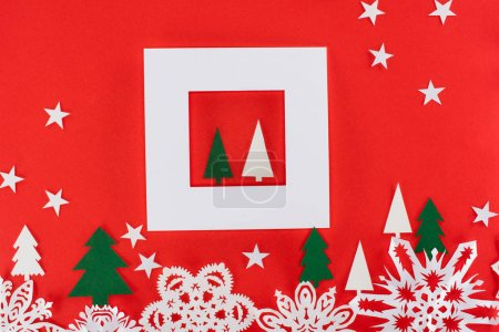 christmas trees in white frame with stars and paper snowflakes around, isolated on red