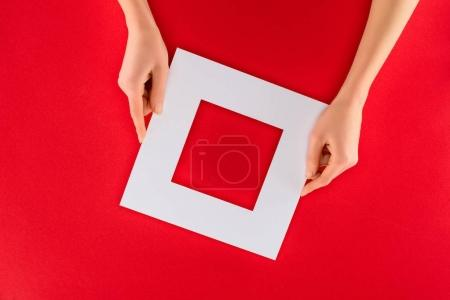 cropped view of female hands with white frame, isolated on red