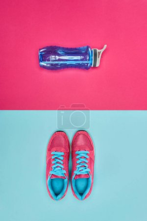 Sports equipment with shoes and water bottle isolated on pink and blue