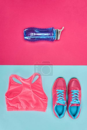 Sports equipment with shoes, water bottle and sports top isolated on pink and blue