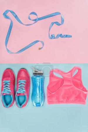 Sports equipment with shoes, measuring tape and sports top isolated on pink and blue