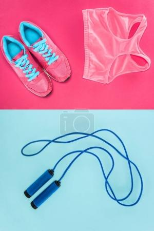 Sports equipment with shoes, skipping rope and sports top isolated on pink and blue