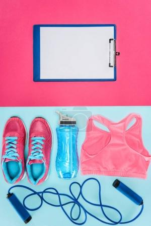 Sports equipment with shoes, skipping rope, sports top and clipboard isolated on pink and blue