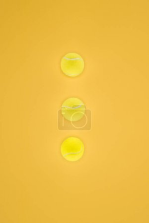 Tennis balls in a row isolated on orange background