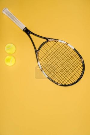 Photo pour Raquette de tennis avec des balles isolées sur jaune - image libre de droit
