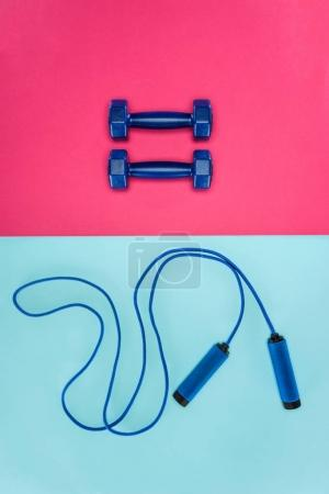 Sports dumbbells and skipping rope isolated on pink and blue