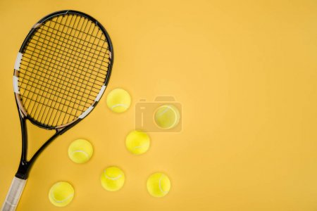 Tennis racket with balls isolated on yellow