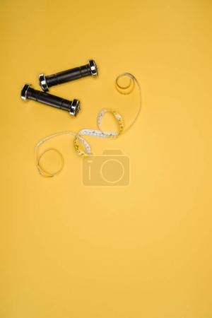 Black shiny dumbbells and measuring tape isolated on yellow