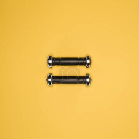 Black shiny dumbbells isolated on yellow background