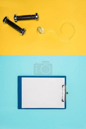Sports dumbbells, measuring tape and clipboard isolated on yellow and blue