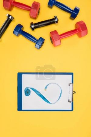 Sports dumbbells and clipboard isolated on yellow background