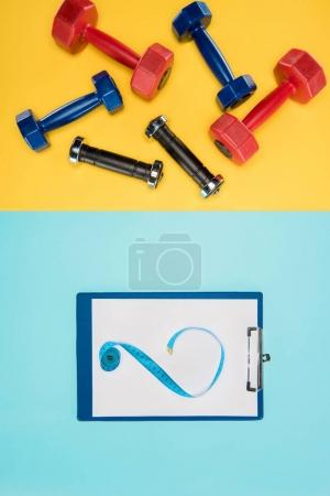 Sports dumbbells and clipboard isolated on yellow and blue