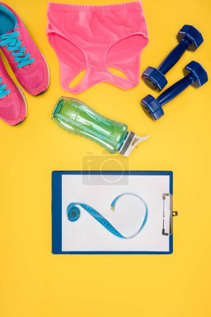 Sports equipment with shoes, dumbbells, sports top and clipboard isolated on yellow