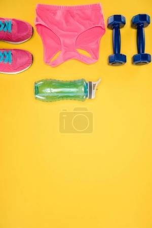 Sports equipment with shoes, dumbbells, sports top and water bottle isolated on yellow