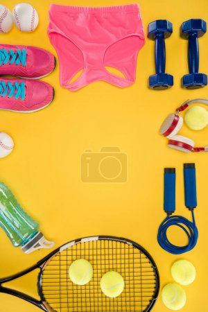Sports equipment with shoes, dumbbells, sports top and headphones isolated on yellow