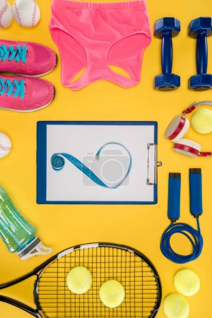 Photo for Sports equipment with shoes, dumbbells, sports top and clipboard isolated on yellow - Royalty Free Image