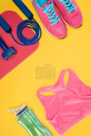 Photo for Sports equipment with shoes, dumbbell, sports top and skipping rope isolated on yellow - Royalty Free Image