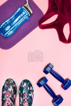 Sports equipment with shoes, dumbbells, sports top and water bottle isolated on pink