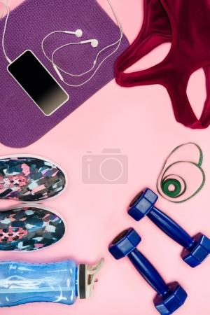 Sports equipment with shoes, dumbbells, sports top and smartphone isolated on pink