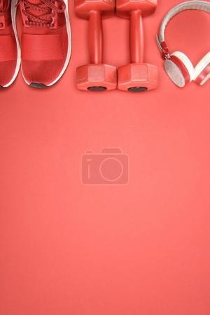 Equipamiento deportivo con zapatos, mancuernas y auriculares aislados en rojo