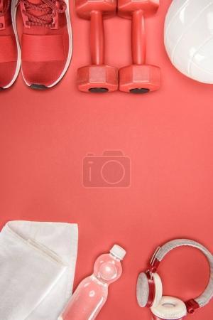 Equipamiento deportivo con zapatos, mancuernas, bola y auriculares aislados en rojo