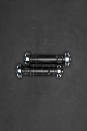 Black shiny dumbbells on black background