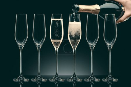 cropped image of woman pouring champagne from bottle into six transparent glasses on black