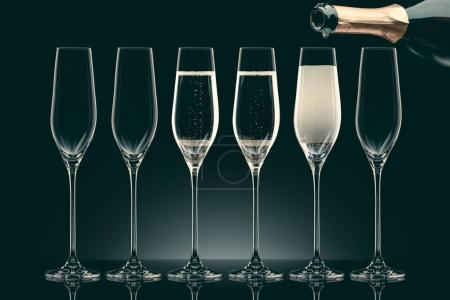 pouring champagne from bottle into six transparent glasses on black