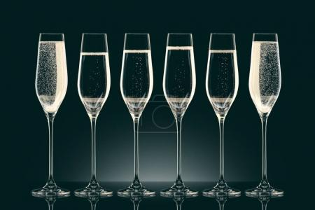 six transparent glasses with champagne on black