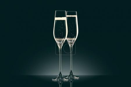 two transparent glasses of champagne on black