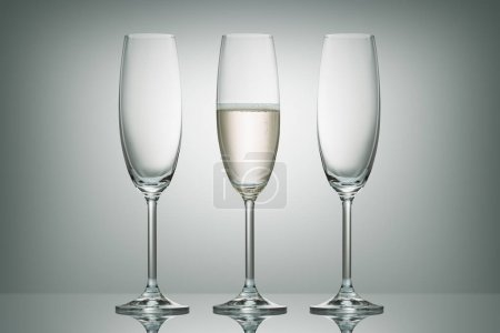 two empty glasses and one glass with champagne on white