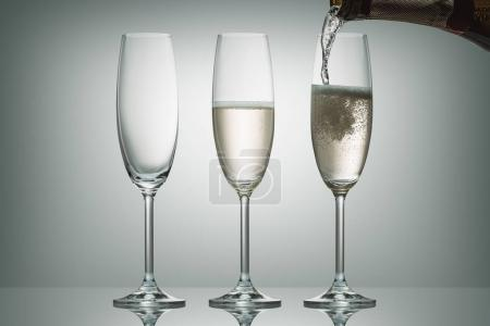 pouring champagne from bottle into three glasses on white