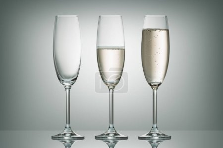 three glasses with different level of champagne on white