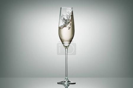 splashing champagne in transparent glass on white