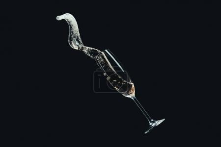 spilling champagne from falling glass isolated on black