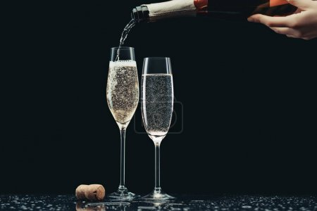 cropped image of woman pouring champagne from bottle into glasses on black