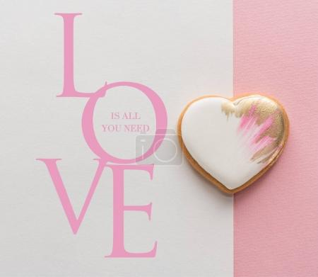 Photo for Top view of glazed heart shaped cookie on pink surface - Royalty Free Image