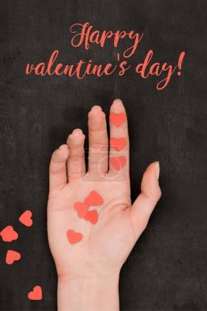 partial view of female hand and red heart shaped confetti on dark background, st valentines day concept